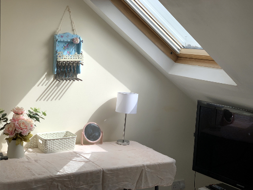 Attic bedroom interior with desk that doubles as dressing table